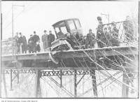 Historic photo from 1912 - Crowd looking at electric automobile in accident on Glen Road Bridge in Rosedale