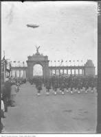 Historic photo from Saturday, August 25, 1928 - Princes Gate with balloon overhead and the Warriors Parade passing through the gates in CNE