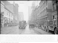 Historic photo from Monday, February 7, 1927 - Grand Opera House on Adelaide St, east, from Bay, noon, slow moving truck forced to use second traffic lane by parked cars, faster traffic in turn forced over to wrong side of street to pass in Downtown