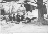 Historic photo from 1907 - Women getting ready to skate on Grenadier Pond with shoes and coats in the trees in High Park